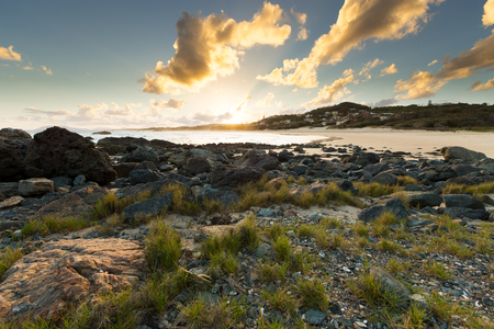 The sun sets on a vibrant beach scene in Port Macquarie, Australia, illuminating the surrounding clouds, coastline and grass tufts in the foreground.