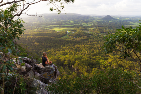 A young man sits, quietly meditating on top of a mountain with expansive views near Noosa Heads, Australia. Stock Photo