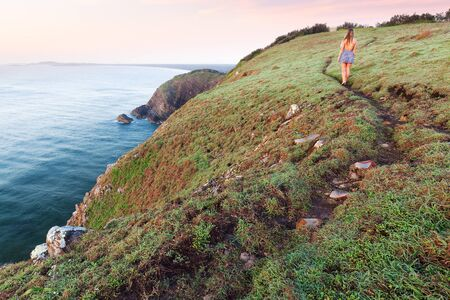 A woman in a dress walks on a winding grassy trail beside a cliff above the ocean at sunrise on an isolated coastline near Port Macquarie, Australia.
