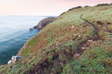 An empty coastal trail on a grassy headland above a cliff and the ocean at sunrise near Port Macquarie, Australia. 版權商用圖片