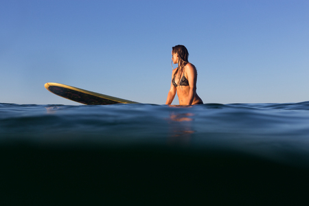 A beautiful female surfer sits on her surfboard in the evening light on the Pacific Ocean.