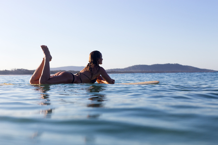 A beautiful female surfer lays on her surfboard on a beautifully calm ocean in Australia.
