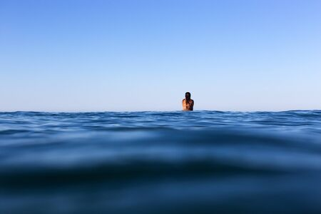 A surfer sits on her board looking towards the horizon, waiting for a wave on a glassy calm ocean in Australia
