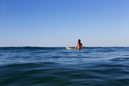 波の穏やかな海に美しいサーファーガールを辛抱強く待ちます。 写真素材 - 82478906