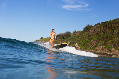 A tanned girl surfs a longboard at a scenic location during a beautiful summer day in Australia. 版權商用圖片