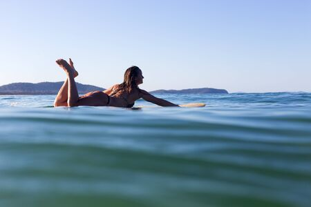A beautiful female surfer is silhouetted by the evening sunlight as she lays on her surfboard in a calm ocean.