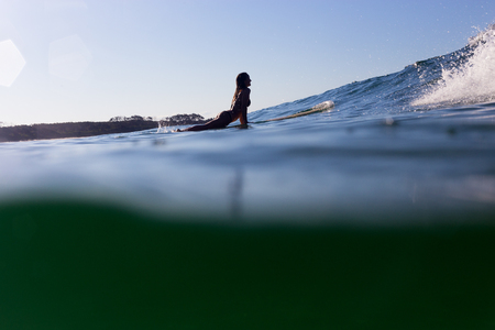 A surfer is back lit by the evening light as she paddles over a cresting wave. 版權商用圖片