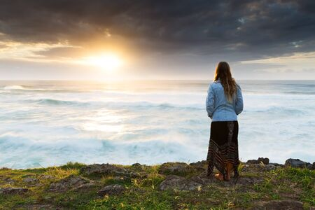 A woman huddles in the cold and watches a bright sunrise over the ocean. 版權商用圖片