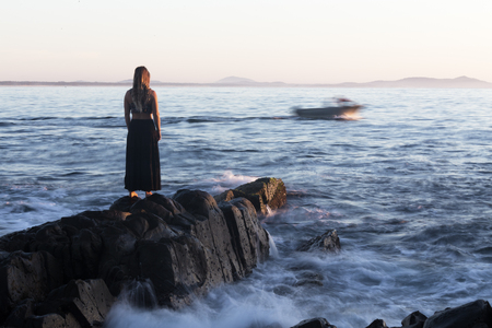 A woman watches from a rocky shoreline as a motion blurred boat goes by, heading out to sea.