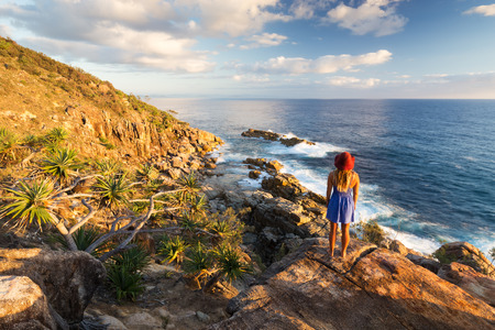 A young woman admires a coastal view over the ocean at sunrise near Coffs Harbour, Australia. 版權商用圖片