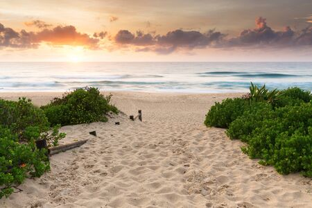 A colourful sunrise over a beautiful ocean scene and a walkway, spotted with footprints in the sand.