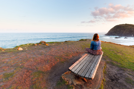 A young woman sits on a wooden park bench and looks over a beautiful ocean scene. 版權商用圖片