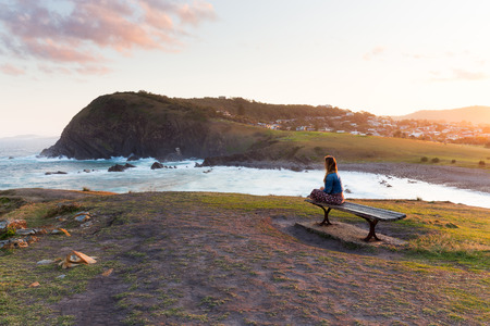A woman sits on a wooden bench and watches the golden sun light disappearing from the beautiful coastline around her. 版權商用圖片
