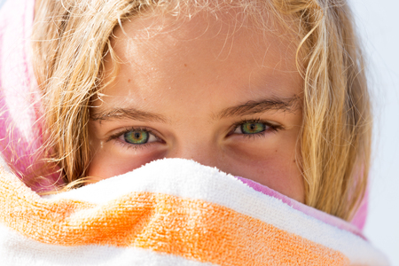 A vibrantly healthy young girl hides her cheeky smile behind a towel while on holidays at the beach.