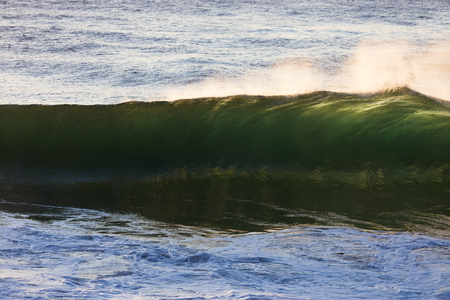 A beautiful, emerald wave is back lit by the bright morning light as it crests and breaks on a shallow sand bar. 版權商用圖片