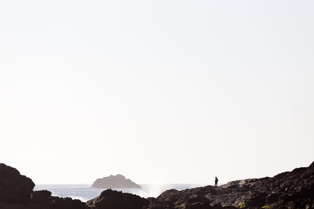A person is silhouetted by bright morning light in a beautiful coastline seascape.