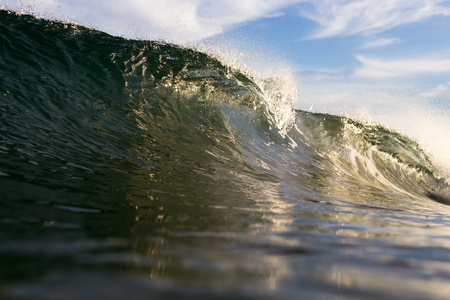 A close up wave breaking in beautiful golden evening light.