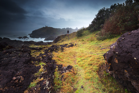 A person looks on as a dark moody storm moves over the rugged coastline that surrounds.