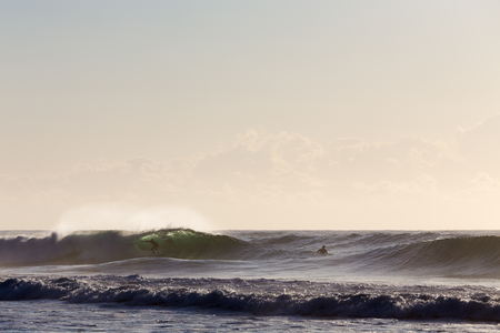 Two surfers enjoy perfect, back lit waves on a bright summer morning in Australia.