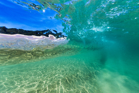 Een onderwaterschot van een golf die in zuiver, duidelijk turkoois water over een zandbodem bij een mooi strand in Australië breken. Stockfoto