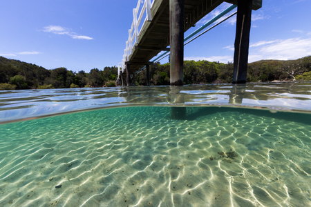 A bridge crosses over beautiful pristine water on a summer day in this underwater split image.