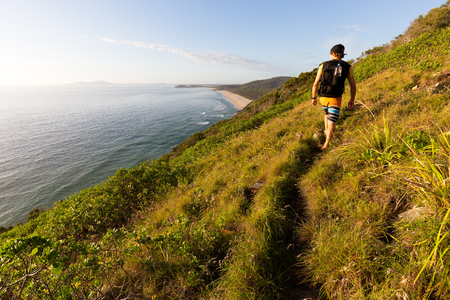 A hiker looking at a beautiful coastline view over the sea during a bright summer morning as he walks on a grassy coastal trail in Australia. Stock Photo