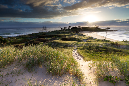 An illuminated trail disappears amongst sand dunes and coastal grass as a bright sunrise bathes the surrounding coastline with intense light. Stock Photo