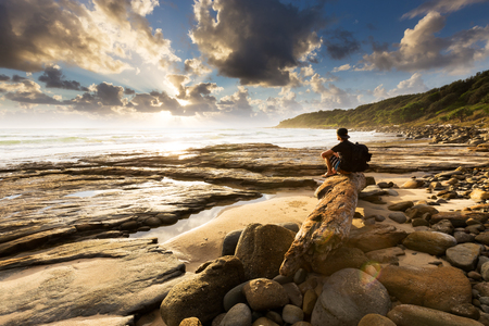 beaming: A person sits on a beautiful rocky beach and watches as the sun bursts through the clouds over the sea in this beautiful seascape.