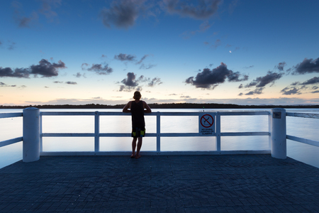 A person watches the sea alone from a pier after dusk in Australia.