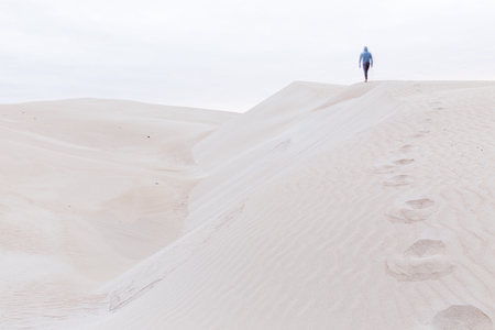 sandhills: A person walks along a sand dune ridge leaving behind a trail of footprints in the sand. Stock Photo