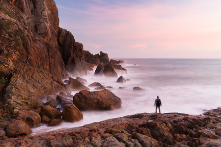 A person is silhouetted by a pink sunrise at the base of a coastal cliff in a beautiful seascape scene. Stock Photo