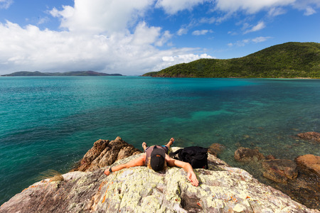 An exhausted traveler rests on a boulder at a beautiful isolated tropical beach in northern Queensland, Australia.
