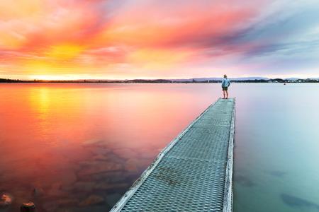 人は、小さな桟橋の端から海を美しい、カラフルな夕日を見守る。