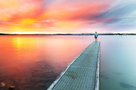 A person watches a beautiful, colourful sunset over the sea from the end of a small jetty. 版權商用圖片