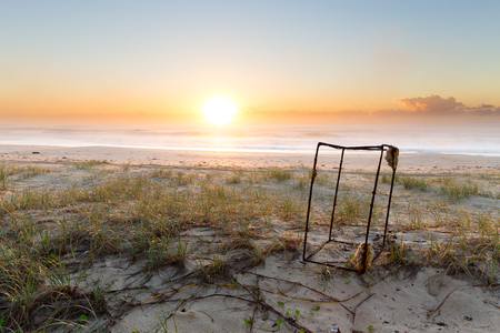 A rusted piece of rectangular ocean litter sits on the beach as the sunrise illuminates the beautiful coastline that surrounds
