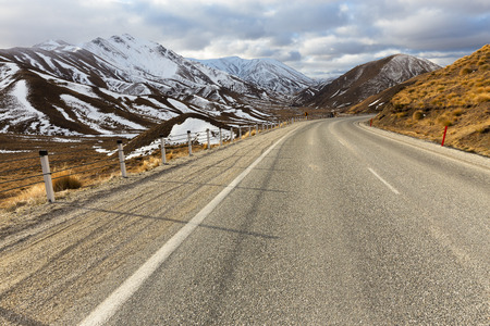 A winding alpine road disappears into the distance amongst snow capped mountains in New Zealand.