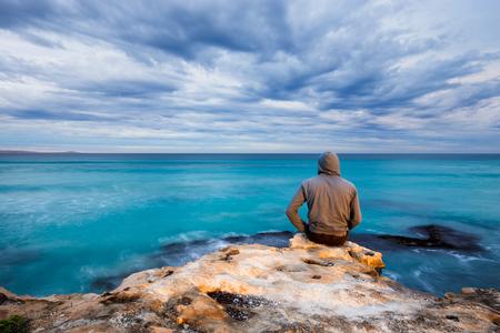 한 남자가 거친 석회암 절벽의 가장자리에 앉아서 남호주의 폭풍우가 치는 바다를 조망합니다.