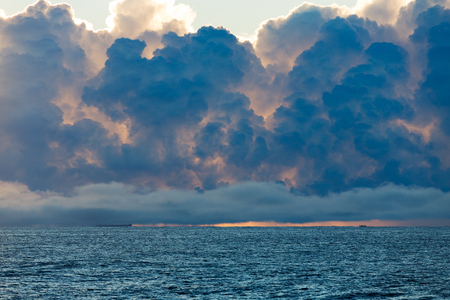 Boats on the horizon are dwarfed by huge storm clouds forming over the ocean.