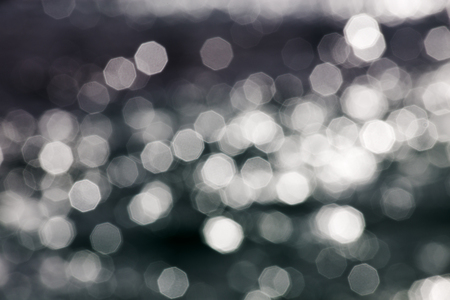 Abstract creative background of aperture sun stars reflecting off of a shimmering sea surface in bright summer light.
