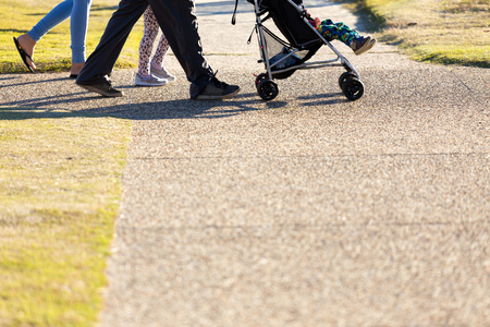 A below waist shot of a family of four, including a baby in a pram, walking and exercising on a city park footpath. 版權商用圖片