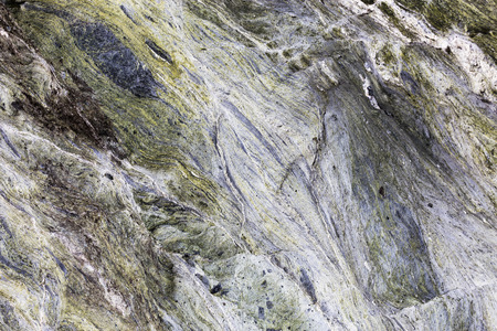 An abstract close up of mineral veins running through green rock in a textured background.