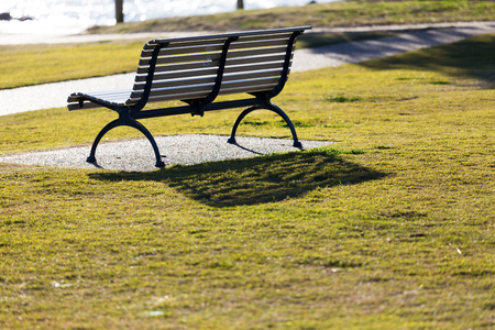 An empty park seat by the sea and beach, backlit by vibrant, bright morning sun light with no people in sight. 版權商用圖片