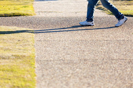 A below waist shot of a man wearing blue jeans and white sneakers walking past a footpath intersection in a city park. 版權商用圖片