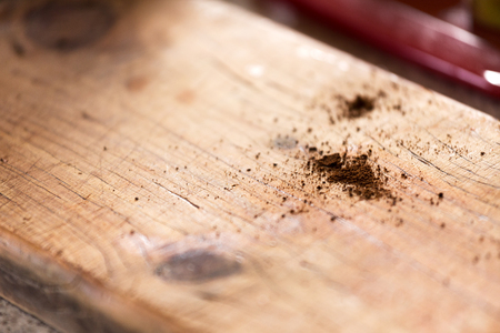 An abstract close up of coffee grinds spilled on a rustic timber cafe bench top with shallow depth of field and space for text or content.