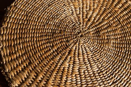 An abstract close up background of a hand woven, spiral, textured wicker grass mat.