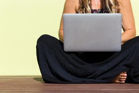 An abstract crop of a beautiful bohemian girl sitting outside on ground with bare feet against a green wall using laptop computer. 版權商用圖片