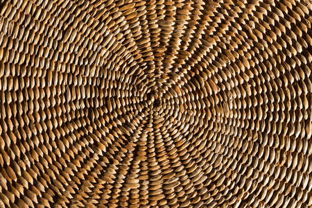 Close up background of an authentic, rustic woven spiral wicker grass mat.