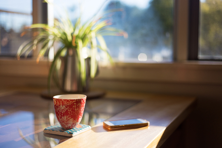 A cup of coffee on a coaster next to smart phone on table with bright morning window light streaming through. 版權商用圖片