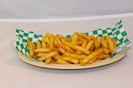 French Fries on a paper plate with checkered napkin Stock Photo