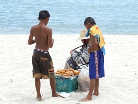 KOH SAMUI, THAILAND - JANUARY 11: Thai women selling foods on the beach to Thai boys on Haad Chewang beach. January 11 2005 on Koh Samui island.  Stock Photo - 7483141